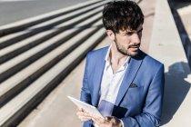 Empresario sosteniendo tableta - foto de stock