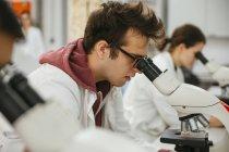 Techniciens utilisant des microscopes en laboratoire — Photo de stock