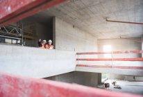 Мужчины, взаимодействующих в строящемся здании — стоковое фото