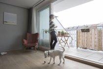 Frau mit Hund steht an Balkontür — Stockfoto