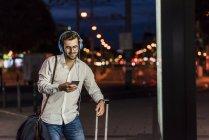 Uomo che utilizza il telefono cellulare in strada — Foto stock