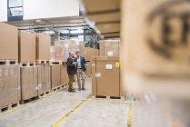 Zwei Männer stehen in Fabrikhalle — Stockfoto
