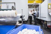 Männer diskutieren unter Maschinen in der Fabrik — Stockfoto
