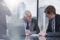 Hommes d'affaires avec ordinateur portable discuter au bureau — Photo de stock