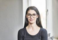 Женщина в очках смотрит в камеру — стоковое фото