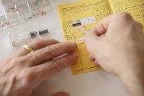 Mains mettre autocollant dans le laissez-passer de vaccination — Photo de stock