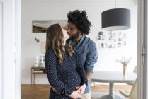 Pregnant couple kissing in living room — Stock Photo