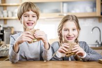 Brother and sister eating sandwiches — Stock Photo
