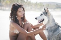 Mexico, Riviera Nayarit beach, young woman sitting with husky dog — Stock Photo