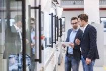Homens com tablet em pé na fábrica — Fotografia de Stock