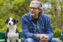 Мужчина сидит с собакой на скамейке — стоковое фото
