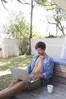 Hombre sentado en la terraza y el uso del ordenador portátil - foto de stock