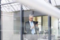 Uomo d'affari utilizzando la tavoletta digitale — Foto stock