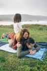 Familia feliz tumbado en la manta - foto de stock