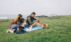 Famiglia con cane seduto sulla coperta — Foto stock