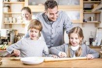 Familie bereitet Baguette in Küche zu — Stockfoto