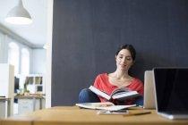 Женщина с книгой и ноутбуком — стоковое фото