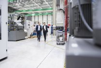 Men walking in factory — Stock Photo
