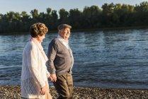 Старшая пара, идущая рука об руку — стоковое фото