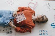Femme couchée entourée de modèles de lettre — Photo de stock