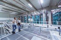 Men standing in high rack warehouse — Stock Photo