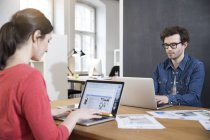 Man and woman using laptops in office — Stock Photo