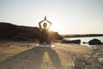 Греция, Крит, женщина, практикующая йогу на пляже на закате — стоковое фото