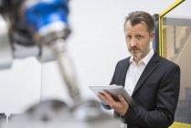 Бизнесмен, контролирующий промышленных роботов — стоковое фото
