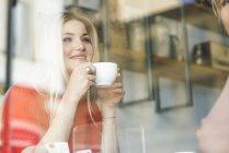 Frau hält Tasse in Café — Stockfoto