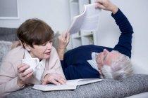 Senior couple lying and reading books — Stock Photo