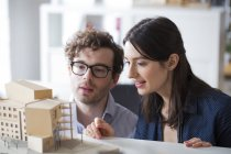 Man and woman discussing architectural model — Stock Photo