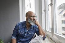 Зріла людина, що сидить у вікні програми, дивлячись турбувався — стокове фото