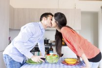 Couple kissing in kitchen — Stock Photo