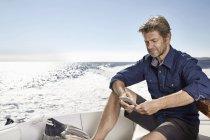 Человек, сидящий на моторной яхте — стоковое фото