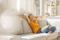 Woman sitting on couch wearing headphones — Stock Photo