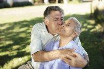 Старший мужчина целует жену в саду — стоковое фото