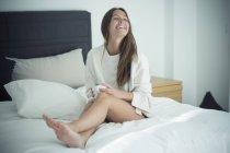 Женщина сидит на кровати с чашкой кофе — стоковое фото