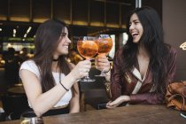 Две счастливые девушки тостуют в баре — стоковое фото
