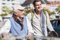 Старший чоловік з велосипеда і онук з скейтборд — стокове фото