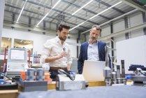 Hommes utilisant un ordinateur portable dans l'usine — Photo de stock