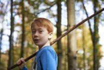 Ritratto del ragazzo dai capelli rossi con il bastone nella foresta — Foto stock
