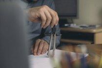 Close-up of man using compasses at desk — Stock Photo