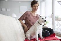 Woman and dog sitting on couch — Stock Photo