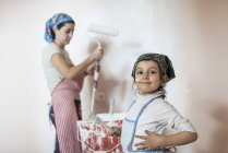 Little girl painting wall with mother — Stock Photo