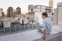 Jovem sentado na balaustrada — Fotografia de Stock