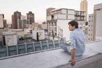 Young man sitting on balustrade — Stock Photo