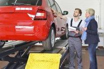 Kfz-Mechaniker mit Kunden stehen — Stockfoto
