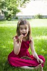 Girl sitting on meadow and eating cherries — Stock Photo