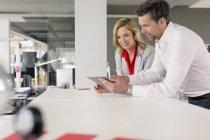 Бизнесмен и деловая женщина используют планшет вместе — стоковое фото