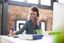 Donna al telefono alla scrivania — Foto stock